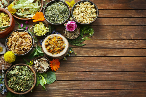 Fotografia  Herb selection and fresh flowers in bowls on wooden background