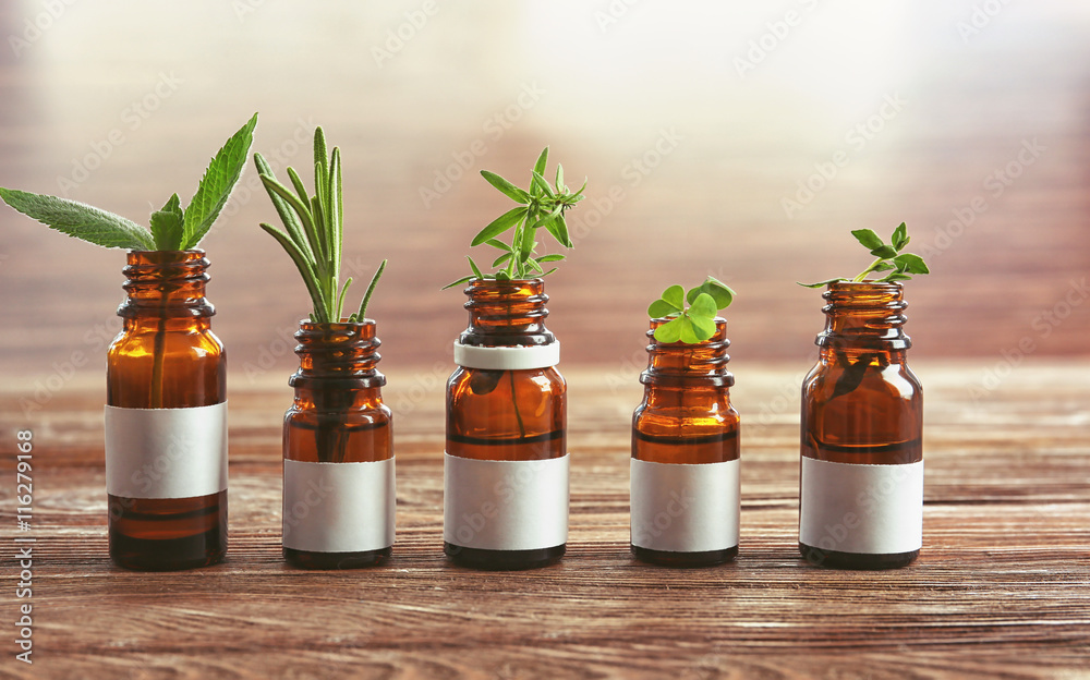 Fototapety, obrazy: Dropper bottles and herbs on wooden table