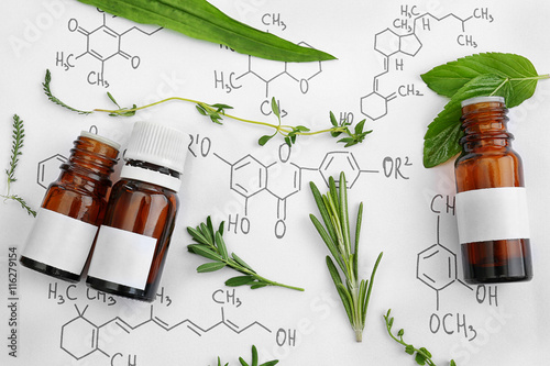Photo  Dropper bottles and herbs on chemical formulas background