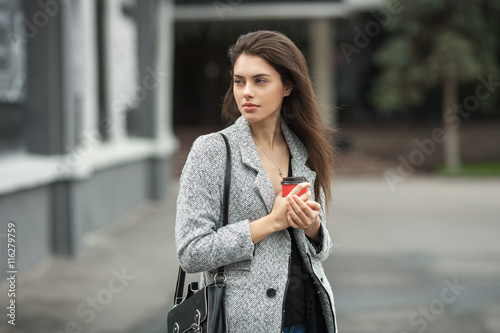 Fotografie, Tablou  Lifestyle fashion portrait of beautiful young brunette woman in grey coat with c