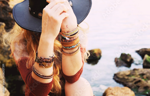 Fotografia, Obraz  Female hands with boho chic bracelets holding black hat