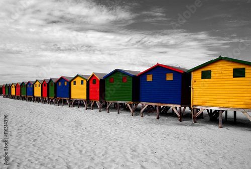 Foto op Plexiglas Zuid Afrika The row of wooden brightly colored huts on Sunrise Beach. Atlantic ocean. Muizenberg, South Africa. Black and white image with colored parts. Artistic retouching.