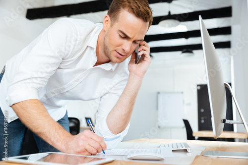 Fotografía  Businessman talking on cell phone and writing in office