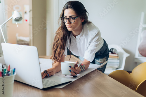 Obraz Running her business from home.young woman working on a computer in her home office - fototapety do salonu