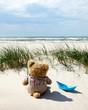 Teddy und Papierschiff am Strand