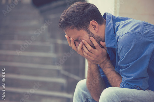 Fotografering stressed sad young crying man sitting outside holding head with hands