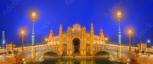 Papiers peints Bleu fonce View of bridges and lights in Spain Square at evening, landmark in Renaissance Revival style, Seville, Andalusia, Spain