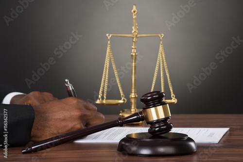 Fotografija  Judge Hands Writing On Document At Desk