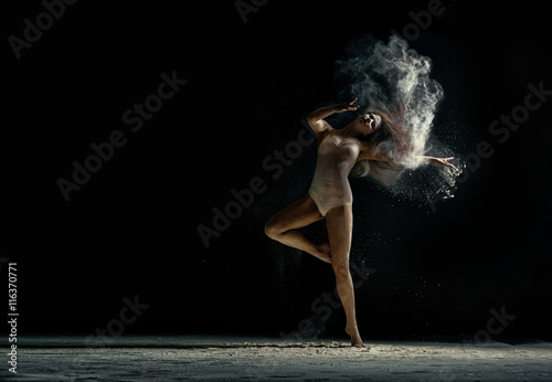 Fényképezés  Amazing photo of graceful woman dancing with dust