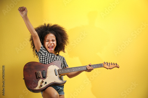 Fotografie, Obraz  Afro-American little girl with curly hair playing guitar on yellow background