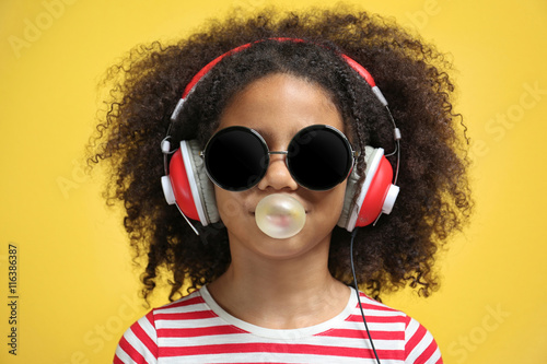 Poster Magasin de musique Afro-American little girl with headphones and sunglasses chewing gum on yellow background