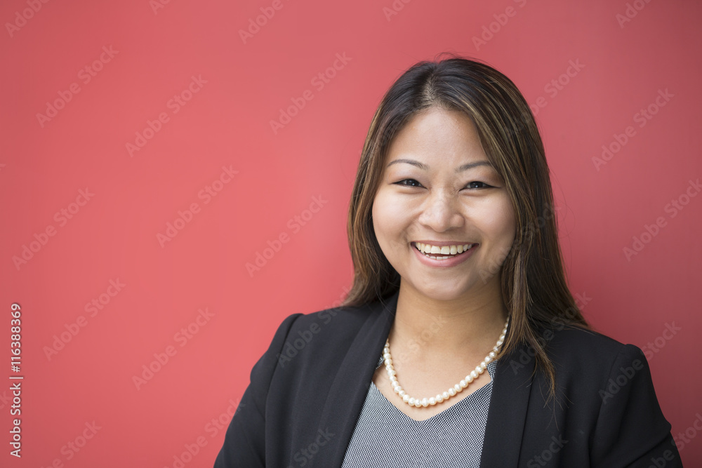 Fototapeta Asian businesswoman leaning against a red wall.