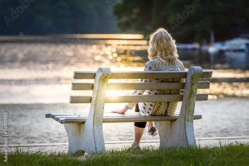 Canvas Print Woman sitting on a bench watching the sun set at a lake on the beach