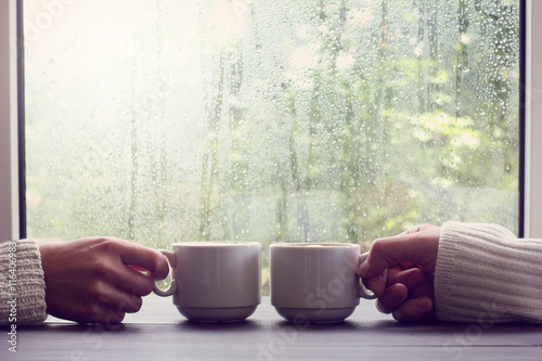 comfortable coffee break for two people/ two white cups in hands on a background of wet window with raindrops