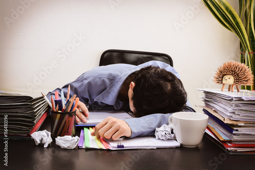 Fototapeta Businessman asleep at office desk with finance sheet calculator and coffee. concept for overworked Dark vintage tone  obraz