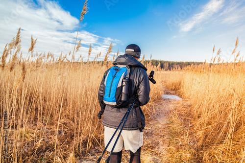 Men hiker in sport uniform with blue backpack and trekking