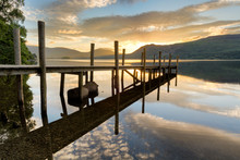 Beautiful Golden Sunrise With Wooden Jetty Reflections In Lake At Derwentwater, Lake District.