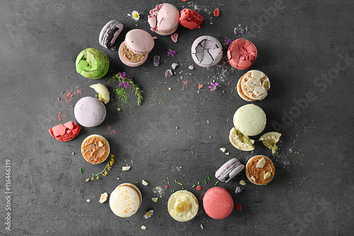 Circle of different colorful macaroons on gray background