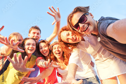 Fotografia  Group of happy young friends doing selfie against the blue sky.