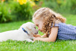 canvas print picture - Little girl with a labrador puppy, outdoor summer