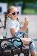 Cute little girl with two long braids, wears sunglasses in a pink frame with glass in the shape of hearts, holds the ice cream in a waffle cone sitting on a Park bench after riding the rollers