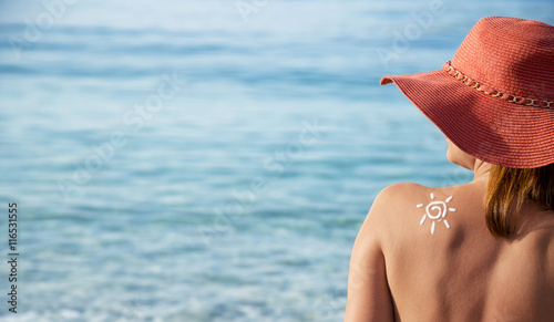 young, beautiful woman sunbathing on summer day in the beach.