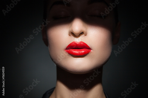 Beautiful model with bright red lips and face half covered in shadow Fototapeta