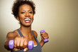 canvas print picture - Happy African American fitness woman lifting dumbbells smiling and energetic.