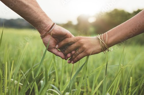 Fotomural Romantic couple holding hands in a field
