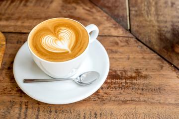 Zatvorite bijelu šalicu kave s latte artom u obliku srca na drvenoj pločici