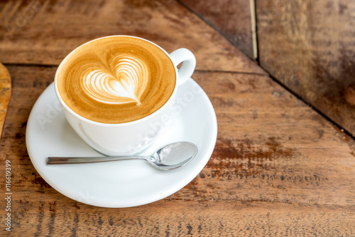 Foto Close up white coffee cup with heart shape latte art on wood tab