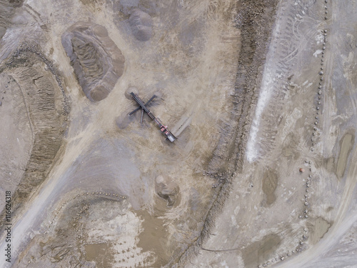 Aerial view of excavator and truck working on the field of sand