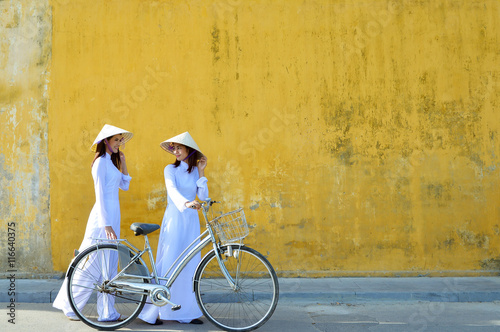 Fotografie, Obraz  Beautiful  woman with Vietnam culture traditional ,vintage style,Hoi an Vietnam