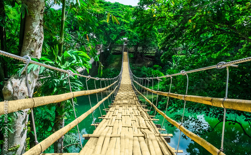 Poster Brug Bamboo hanging bridge over river in tropical forest