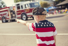 Boy Watching A Firetruck Drive By During A Parade Procession During An Independence Day Parade In A Small Town In The USA