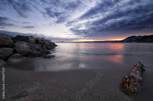 Sunset on Garda Lake, Italy, panoramic view from the sand beach under a cloudy s Poster