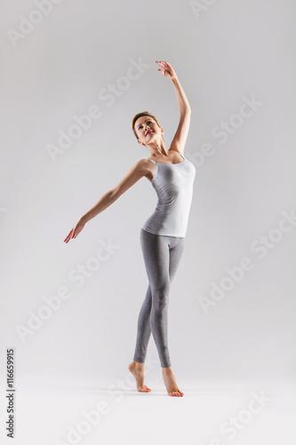 Leinwand Poster  Beautiful young woman doing yoga on a gray studio background