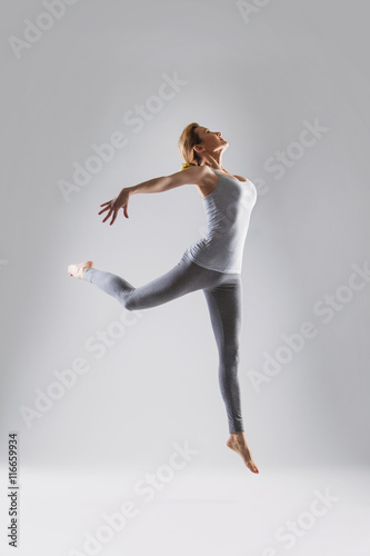 Foto  Beautiful young woman doing yoga on a gray studio background