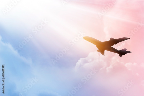 obraz lub plakat Airplane in the sky and colorful clouds in sunset