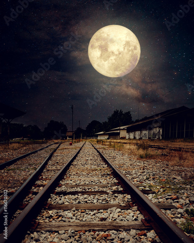 Foto auf Leinwand Eisenbahnschienen Beautiful countryside Railroad with Milky Way star in night skies, full moon - Retro style artwork with vintage color tone (Elements of this moon image furnished by NASA)