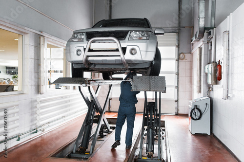 Fotografía  Mechanic inspecting car suspension system of lifted automobile at repair service station