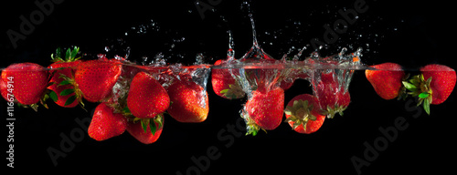 Poster Fruits Strawberries splashing into water on a black background