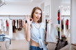 Woman with shopping bag showing ok sign in clothes shop
