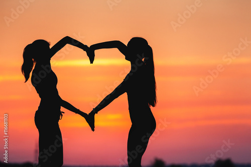 Landscape with silhouette of young sporty women holding hands in heart shape on the background of colorful sky at sunset in summer time. Happy girls. Concept background for design