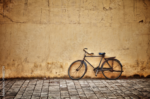 Tuinposter Fiets Old vintage bicycle near the wall