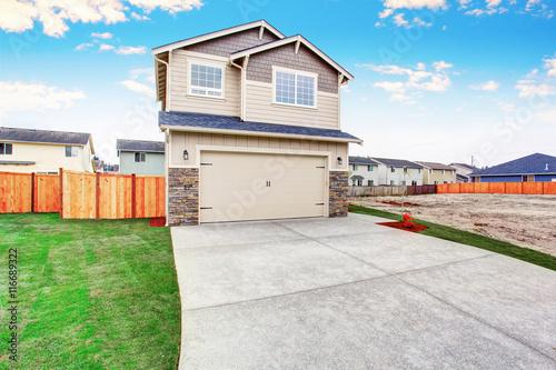 Obraz American house exterior with beige trim, garage with concrete driveway - fototapety do salonu