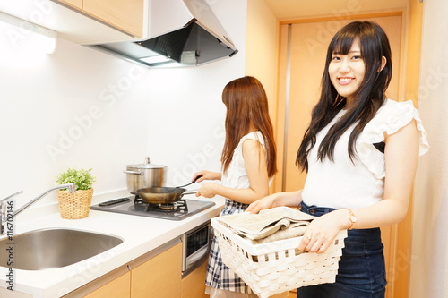 two young japanese women cooking in kitchen シェアハウスの台所で料理