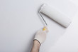 Leinwanddruck Bild - Close up of painter arm painting a wall in gray with paint roller