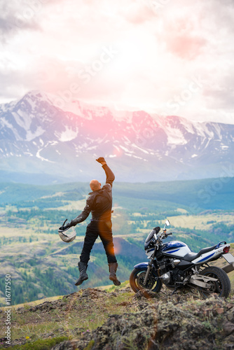 Bald rider jumping with hand raised near motorcycle on backgroun Canvas Print