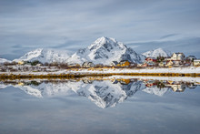 Reflection Of Snow Capped Mountains And Buildings In Lake, Norway